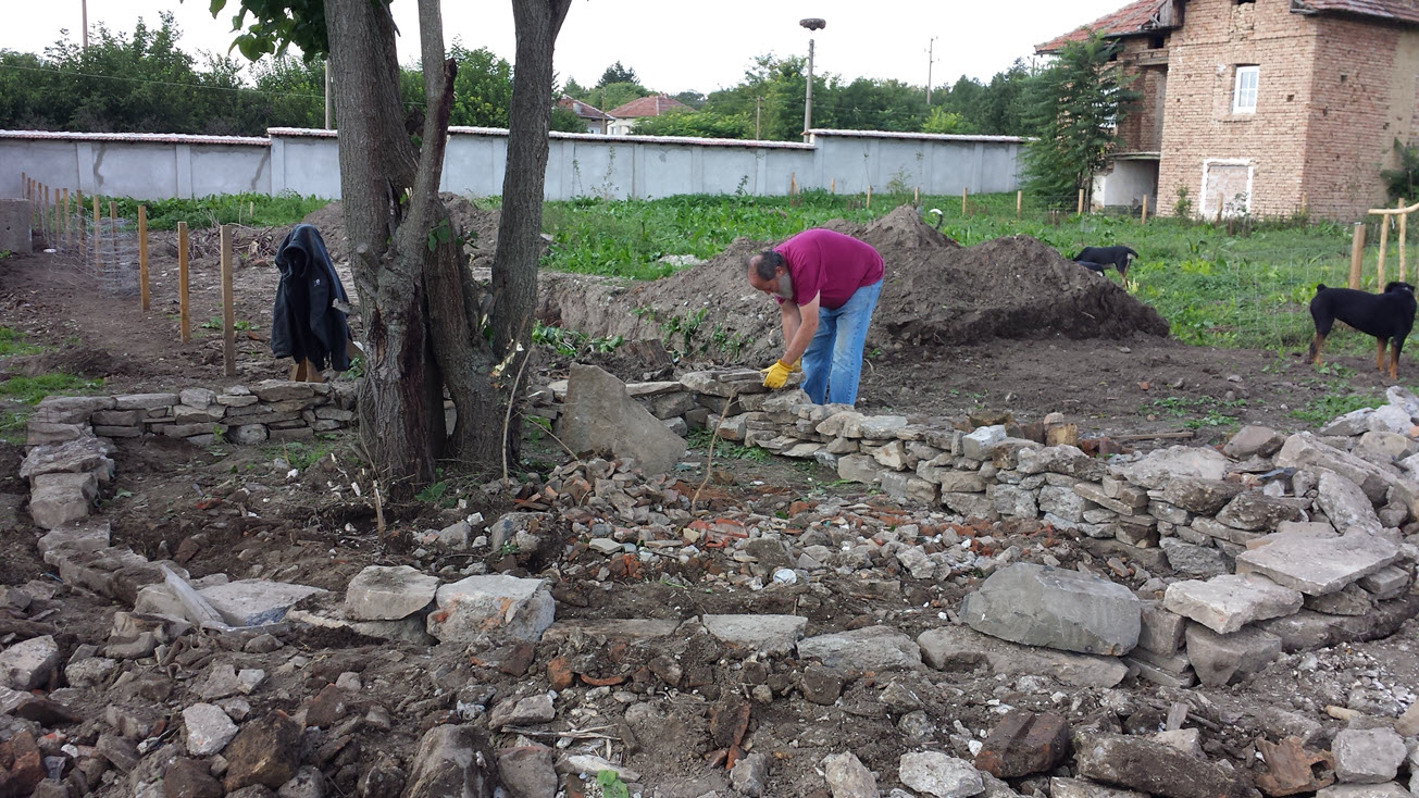 Building the stone / rock / rubble wall around what will be a new flower bed.